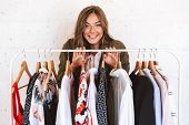 Lovely young woman clothes designer standing at the clothes rack indoors poster