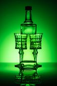 Bottle Of Absinthe With Crystal Glasses On Mirror Surface And Dark Green Background poster