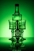 Bottle Of Absinthe With Crystal Glasses On Reflective Surface And Dark Green Background poster