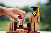 Student Sign Wood With Graduation Cap On Wooden Square Blocks Tower Blur Hands. Spelled Out Letter E poster