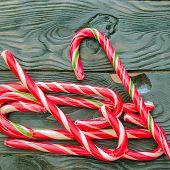 Christmas Sweetness. Festive Caramel Christmas Staffs Lie A Heap On A Dark Wooden Surface. Concept O poster