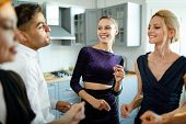 Two glamorous girls and their friends standing in circle and dancing in the kitchen at home party poster
