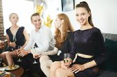 Cheerful and glamorous girl with flute of champagne sitting on sofa with her friends on background a poster