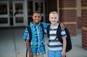 Portrait of Two diverse school kids standing outside their elementary school building. Back to schoo poster