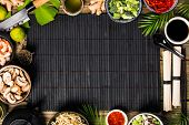 Asian cuisine ingredients on bamboo mat over old wooden background, top view. Vegetables, spices, sh poster