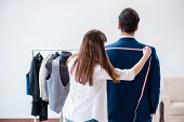 Professional tailor taking measurements for formal suit poster