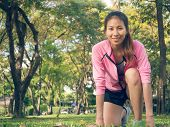 Asian Young Woman On Mark To Set Ready For Jogging Exercise To Buld Up Her Body On Glass In Warm Lig poster