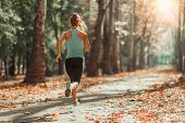 Woman Jogging Outdoors In The Fall poster