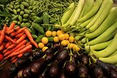 stock photo of brinjal  - Mix of fresh vegetables on a colorful display in a local Indian market - JPG