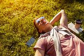 Handsome College Man Chilling In Spring Campus Park. Happy Guy Student Lying On Grass With His Phone poster
