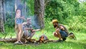 Add Some Wood To Fire. Friends Hang Out Near Bonfire Picnic. Company Youth Camping Forest Prepare Bo poster