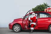 Authentic Santa Claus In Car With Gift Boxes And Christmas Tree, View From Outside poster