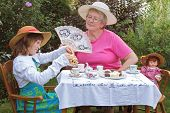 pic of polite girl  - A charming spring garden is a perfect setting for a loving grandmother and her 6 year old granddaughter to have a tea party - JPG