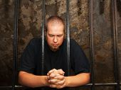 foto of repentance  - Young man praying staying behind the bars - JPG