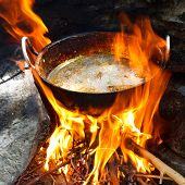stock photo of skardu  - Frying potatoes in a pan over campfire - JPG