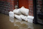 stock photo of sandbag  - Sandbag barrier in doorway of flooded street in York - JPG