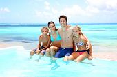 picture of infinity pool  - Family sitting on the side of an infinity pool - JPG