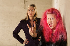 stock photo of spoiled brat  - Teenager in pink hair with disapproving mother in background - JPG
