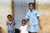foto of overpopulation  - Three black African girls sisters from a larger family by their house - JPG