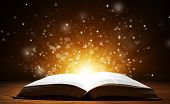picture of bible story  - Old open book with magic light and falling stars on wooden table - JPG