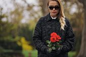 pic of graveyard  - Portrait of young woman in black dress at graveyard holding fresh flowers - JPG