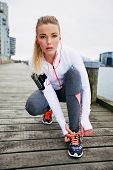 stock photo of lace  - Pretty young woman tying her shoe laces before a run - JPG