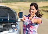 stock photo of accident emergency  - Cheerful woman calling to car insurance service after accident or engine breakdown during roadtrip - JPG