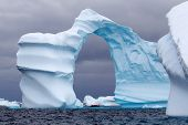 stock photo of arch  - Huge Arch Shaped Iceberg in Antarctic waters with a boat in the distance - JPG