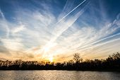 picture of unnatural  - beautiful sunset over the lake with what looks like manufactured cloud formations from airplanes all over the area with metallic shiny colors - JPG