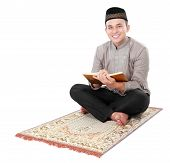 pic of quran  - muslim man holding and reading quran isolated over white background - JPG