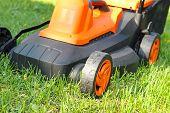 stock photo of grass-cutter  - closeup of electric lawnmower on green grass - JPG