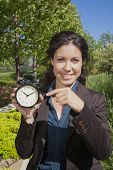 image of fussy  - businesswoman with big clock in exterior background - JPG