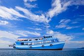 picture of sea-scape  - passenger wooden boat floating on blue sea water with beautiful sky - JPG