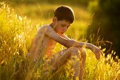 stock photo of beatitudes  - oy sitting and relaxing in the grass on a sunset - JPG