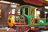 stock photo of chug  - Colorful Child Train Ride in Amusement Park Setting - JPG