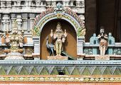 picture of glorious  - Lord Murugan Statue on glorious covered walkway with part of the eastern Gopuram of Annamalaiyar temple in background - JPG