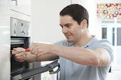 stock photo of oven  - Repairman Fixing Faulty Domestic Oven In Kitchen - JPG