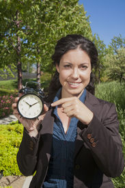 picture of fussy  - businesswoman with big clock in exterior background - JPG