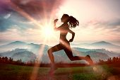 stock photo of ponytail  - Full length of healthy woman jogging against sun shining over mountains - JPG