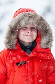 picture of down jacket  - Cute boy in a red parka down jacket outdoors on beautiful winter snow day - JPG