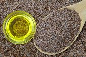 stock photo of flax seed oil  - A bowl of cold pressed Linseed yellow oil on flaxseed background - JPG