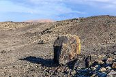 foto of volcanic  - Volcanic bomb in front of volcano Montana Colorada in Lanzarote Canary Islands Spain - JPG