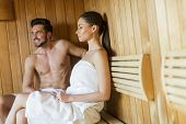 foto of sauna  - Young couple sitting on a wooden bench at the sauna - JPG