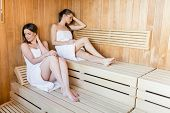 stock photo of sauna woman  - Young women relaxing on wooden bench at the sauna - JPG