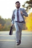 picture of running-late  - Businessman running in park - JPG