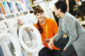 picture of supermarket  - Young female seller assistant helps woman to choose washing machine in home appliance shopping mall supermarket - JPG