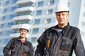 foto of real-estate-team  - Team of smiling foreman builders workers in protective uniform at construction building site - JPG