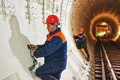 picture of tunnel  - Tunneller worker installing fixture in underground subway metro construction site - JPG