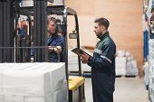 stock photo of forklift  - Warehouse worker talking with forklift driver in ware house - JPG