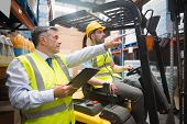 pic of forklift driver  - Forklift driver talking with his manager in a large warehouse - JPG